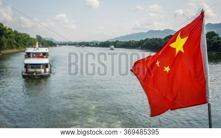 Red Chinese National Flag Fluttering On A Mast On The Deck Of Sightseeing Boatt Full Of Tourists Dep