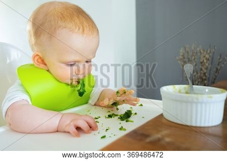 Naughty Baby Making Mess While Eating Broccoli Vegs And Soup. Little Child Wearing Plastic Bib, Sitt
