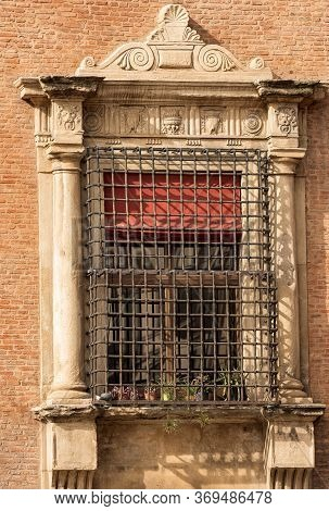 Ancient Window With Metal Grate, Columns And Bas Reliefs, Accursio Palace, Town Hall In Downtown Of