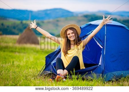 Girl Tourist Meets Morning With Outstretched Arms In Tent With Beautiful Mountains View.