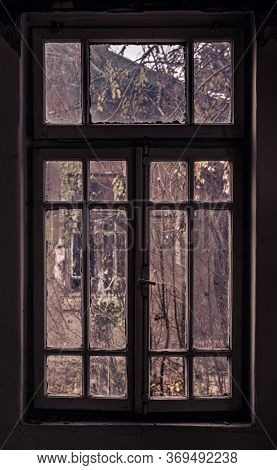 Windows Of An Abandoned Building With Wooden Frames And Broken Glasses.