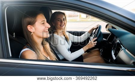 Portrait Of Female Driver Talking To Smiling Woman Sitting On Passenger Seat While Driving A Car