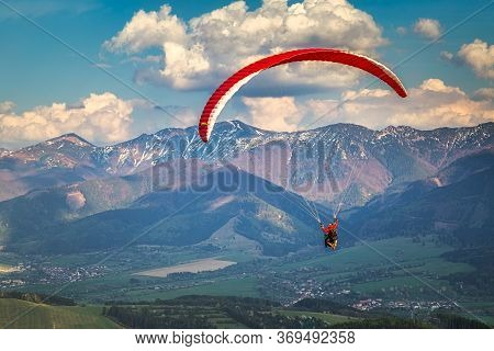 Flying Paraglider From The Stranik Hill Over The Mountainous Landscape Of The Zilina Basin In The No
