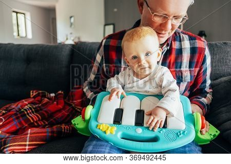 Portrait Of Baby Girl And Her Grandpa Playing With Piano Toy. Little Child Sitting On Mans Lap In Li