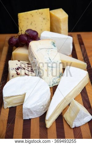 Different Cheeses Laying On Wooden Board. Brie, Camembert, Parmesan Collection. Studio Shot. Selecti