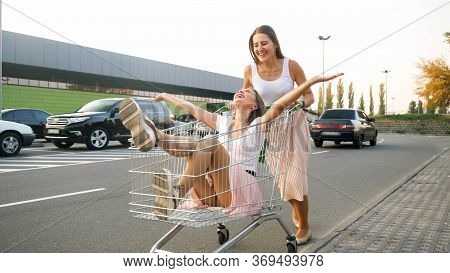 Two Happy Laughing Girls Having Fun On Shopping Mall Car Parking And Riding In Shopping Cart