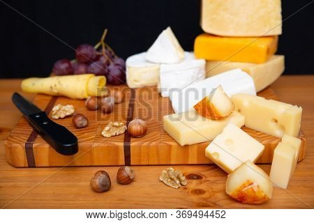 Different Cheeses, Grapes And Nuts Laying On Wooden Board. Parmesan, Edam, Gouda. Studio Shot. Selec