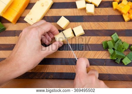 Female Hands Cutting Cheese On Dices With Knife. Edam, Gouda, Cheddar. Studio Shot. Selective Focus.