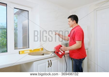 Middle Aged Caucasian Man Cutting Hole In Worktop For Round Kitchen Sink