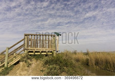 The Wooden Animal Shelter And Birding Spotting Scope Camera, Landscape Of Golden Grass And Small Lak