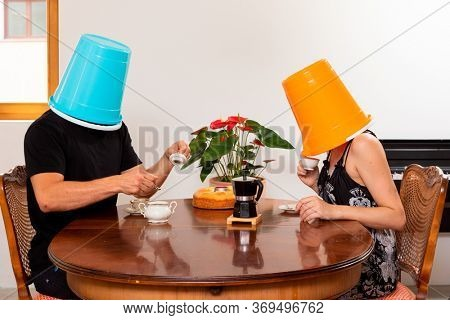 Young loving couple drinks coffee in the dining room with a bucket on their heads. Unreal situation and concept of non-communication