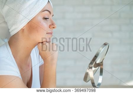 A Sad Woman Sits At A Table And Looks In The Mirror. A Miscarriage Of A Girl With Hormonal Problems