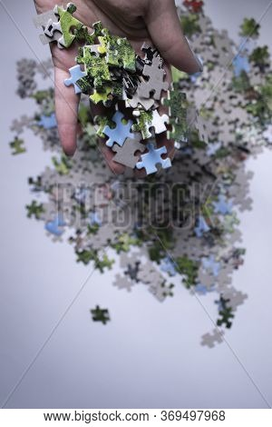 Hand Holding Multicoloured Puzzles On A White Background. Isolated. Top View, Copy Space