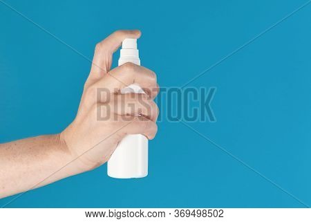 Hand Holding Up A White Spray Bottle, Isolated Against A Blue Background