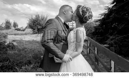 Black And White Portrait Of Happy Newly Married Couple Kissing At Countryside
