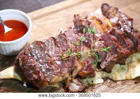 Steak Roast On A Wooden Board With Sauce And Salt. Delicious Steak. Beef Steak On Wooden Plate. Medi