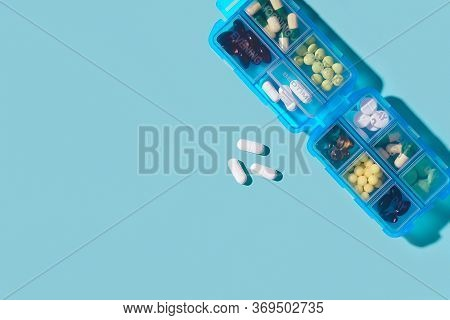 Prescription Pills And Vitamins In A Blue Pill Box On Neo Mint Color Background. Flat Lay Photo, Spa