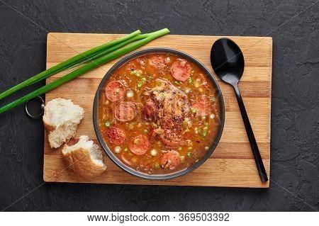 Chicken And Sausage Gumbo Soup In Black Bowl On Dark Slate Backdrop. Gumbo Is Louisiana Cajun Cuisin