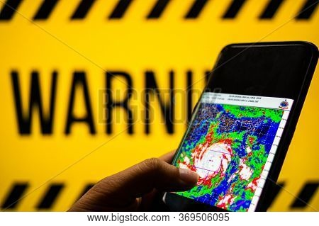 Mobile Phone Logged Into Photo Of Cyclone With Warning Background