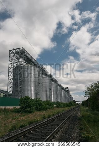 A Large Modern Plant For The Storage And Processing Of Grain Crops.  Silver Silos Granary In A Row.