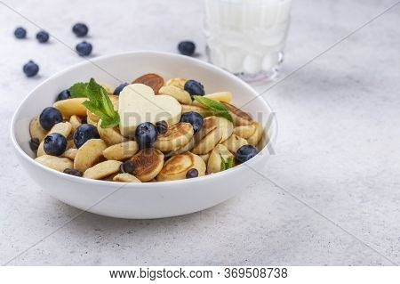 Mini Pancake Cereal In A Bowl On Grey Concrete Background. Trendy Mini Pancakes With Blueberry And C