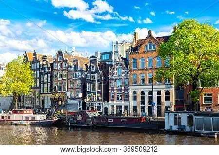 Amsterdam Cityscape View Of The Canal In Summer With Blue Sky, Houseboat And Traditional Old Houses.