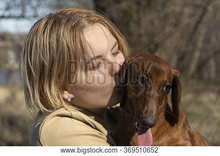 A Young Girl Kisses And Hugs A Dachshund Puppy, Holds It In Her Arms. Walk With Your Pet. The Concep
