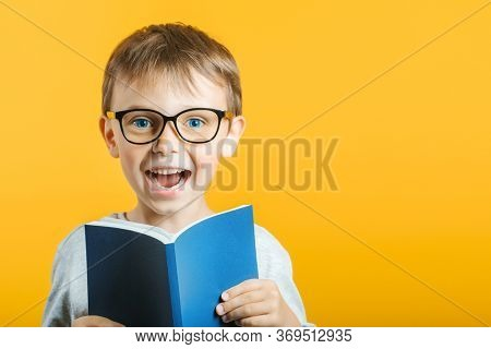 child reads a book against a bright wall