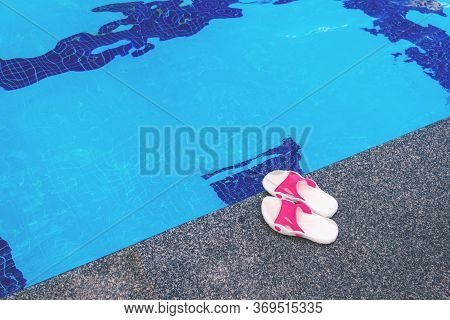 Summer Background With White-pink Slippers For The Pool, Near The Pool.