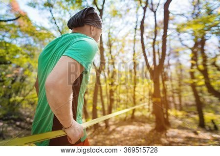Portrait Of A Bearded Athletic Man Engaged In Slack Next To A Stretched Sling For Balance In The Aut
