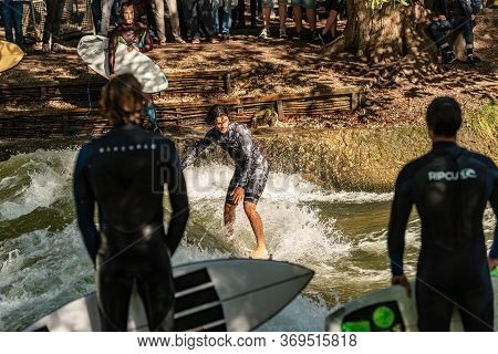 Munich, Germany - Sept 8, 2018: Man Surfing In The Waves Of The Eisbach River In Munich. It Forms A