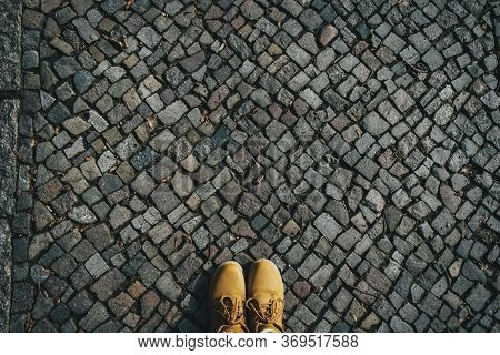 Stones Pattern Background, Cobblestone Sidewalk With Feet In Yellow Shoes