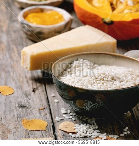 Ingredients For Cooking Pumpkin Risotto. Raw Uncooked Risotto Rice In Ceramic Bowl, Sliced Pumpkin,