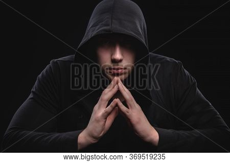 A Low-key Studio Portrait Of A Large Man In A Hood Sits Pondering. Sex Faces In The Dark Hacker Stea