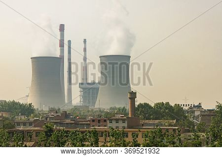 Xian, China - May1, 2010: Cooling Towers And Chimneys Of Power Plant Under Gray And Yellowish Smoggy