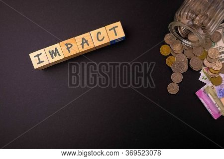 Wooden Cubes Over Dark Background With Texts Impact. Coins And Currencies Visible. Conceptual On Imp
