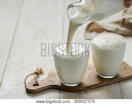 Pouring Homemade Kefir, Buttermilk Or Yogurt With Probiotics. Yogurt Flowing From Glass Bottle On Wh