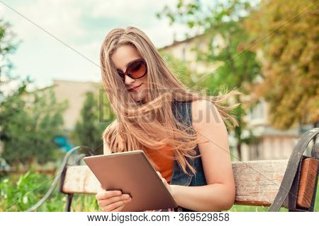 Working On Pad. Beautiful Woman Looking At Digital Tablet Outdoors And Smiling Slight Smile. Mixed R