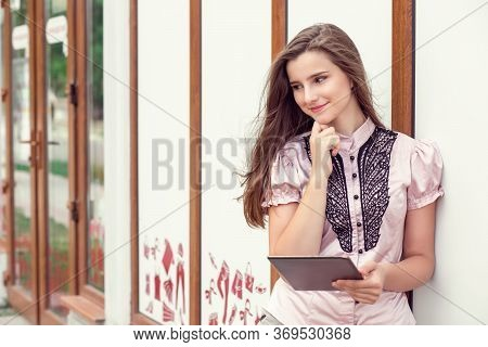 Daydreaming With Pad. Pensive Woman Teenage Girl Female With A Digital Tablet Standing Near A City S