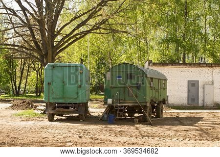 Two Green Wagon Trailers In Which Builders Rest And Sleep. Overhaul In The Courtyard Of An Apartment
