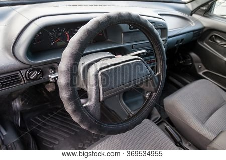 A Close-up Of The Interior Of A Russian Driver's Car Seat And Steering Wheel Made Of Plastic And A C