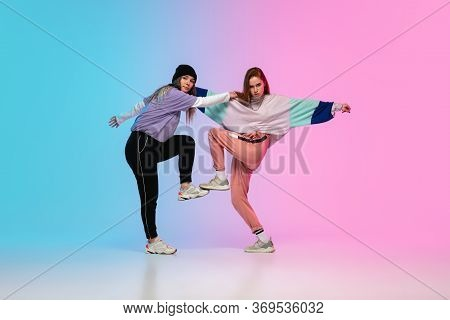 Flexible. Sportive Girls Dancing Hip-hop In Stylish Clothes On Colorful Gradient Background At Dance