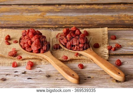 Dried Strawberries In A Wooden Ladles With An Old Wooden Background.
