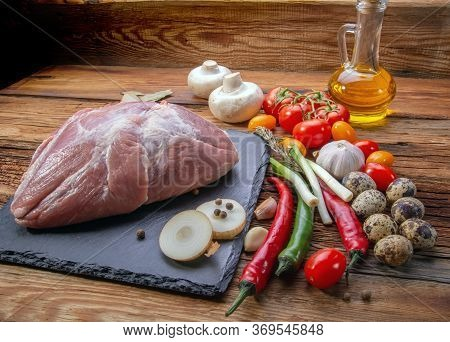 Pork Tenderloin In One Piece On A Slate Stone With Fresh Vegetables And In The Village Style