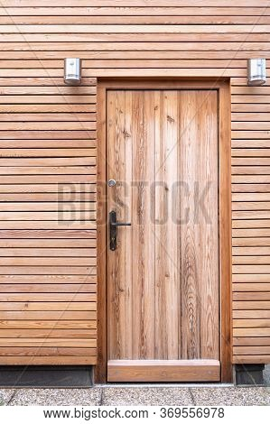View Of The Front Door And The Wall Of The Building Which Are Made Of Natural Wooden Boards.