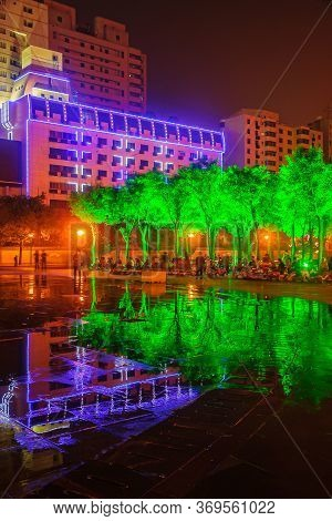 Xian, China - May 1, 2010: Black Night Scene. Lighted Up Tall Buildings Behind Green Lighted Trees W