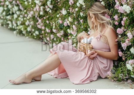 Young Woman Is Breastfeeding A Baby On Nature.
