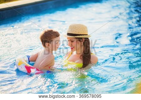 Beautiful Mother In A Yellow Bathing Suit And Hat Swims In The Pool With Her Son In A Rubber Ring. H