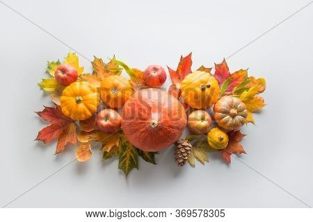 Thanksgiving Day. Fall Decor Of Pumpkins, Leaves, Apples On Grey. View From Above. Centerpieces.
