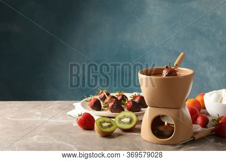 Composition With Ingredients For Chocolate Fondue On Gray Table. Cooking Fondue